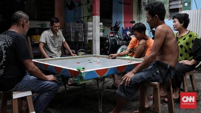 Warga RW 01 Kelurahan Pegangsaan, Kecamatan Menteng, melakukan aktivitas bermain karambol di depan rumah. Kawasan pemukiman kumuh di daerah Cikini Jakarta Pusat ini dihuni 100 Kepala Keluarga. (CNNIndonesia/Andry Novelino)