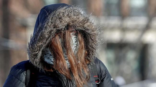 Seorang pelajar berpakaian tebal untuk menghadapi cuaca yang mencapai di bawah nol derajat celcius di Minnesota, Minneapolis, Amerika Serikat. (REUTERS/Eric Miller)