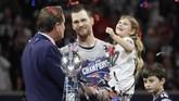 Tom Brady menggendong putrinya ketika merayakan gelar Super Bowl 2019. Terlihat trofi Vince Lombardi di dekat Brady. (REUTERS/Kevin Lamarque)