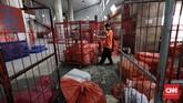 Petugas mengangkut barang paket yang akan didistribusikan ke penerima di unit paket kantor Pos Indonesia. (CNNIndonesia/Safir Makki)