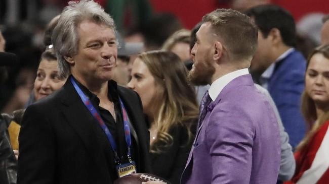 Jon Bon Jovi berbicara dengan petarung UFC Conor McGregor sebelum pertandingan New England Patriots vs Los Angeles Rams. (REUTERS/Mike Segar)