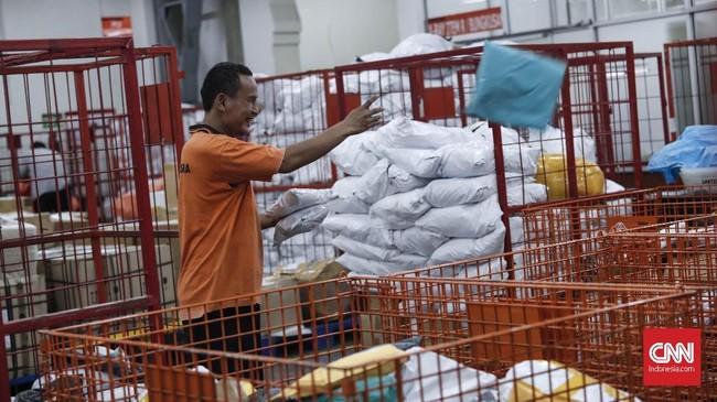 Petugas menyortir barang paketan yang baru tiba dari luar negeri di kantor Pos Indonesia. (CNNIndonesia/Safir Makki)