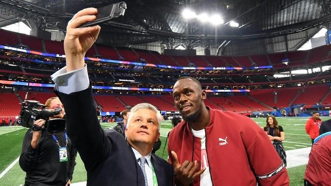 Peraih medali emas Olimpiade Usain Bolt melakukan selfie dengan penggemar sebelum pertandingan Super Bowl 2019. (REUTERS/Christopher Hanewinckel-USA TODAY Sports)