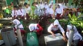 Sejumlah siswa Sekolah Dasar membersihkan tempat sampah untuk pemberantasan sarang nyamuk di SDN Balungbang Jaya 3, Kota Bogor, Jawa Barat, Jumat (1/2/2019). Pemerintah Kota Bogor mencanangkan Gerakan SerentakPemberantasan Sarang Nyamuk (PSN) untuk menekan kasus Demam Berdarah Dengue (DBD) di wilayah Bogor. ANTARA FOTO/Yulius Satria Wijaya