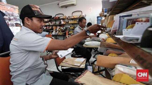 Petugas pengantar pos memyortir surat yang akan dikirimkan ke penerima di kantor Pos Indonesia. (CNNIndonesia/Safir Makki)