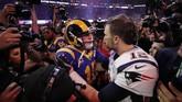 Pemain bintang New England Patriots Tom Brady coba menghibur pemain Los Angeles Rams Jared Goff usai memenangi Super Bowl 2019. (REUTERS/Mike Segar)