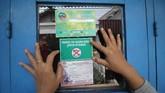 Seorang kader Ibu Memantau Jentik (Bumantik) menempelkan stiker bebas jentik nyamuk di salah satu rumah warga saat Gerakan Pemberantasan Sarang Nyamuk di Surabaya, Jawa Timur, Jumat (1/2/2019). ANTARA FOTO/Moch Asim/nz.