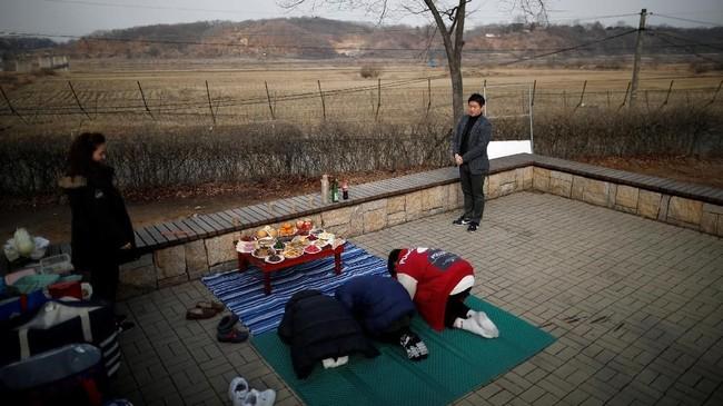Di Korea, sebuah keluarga yang memiliki anggota keluarga Korea Utara menggelar upacara petingatan kemartian di depan pagar kawat berduri dekat zona demiliterisasi yang memisahkan kedua Korea. (REUTERS/Kim Hong-Ji)