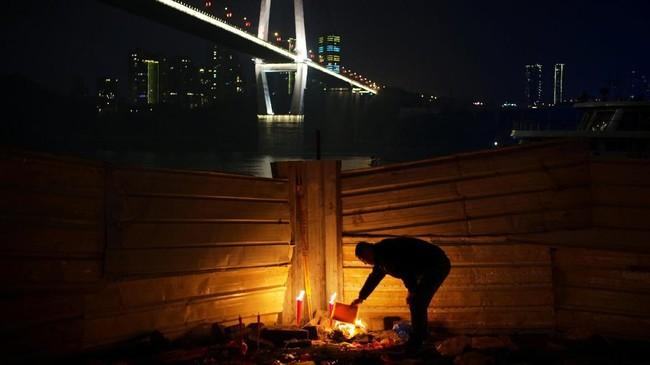 Seorang lelaki membakar kertas-kertas dupa untuk berdoa agar mendapat keberuntungan pada malam Tahun Baru Imlek Babi Cina, di sebuah kuil dekat jembatan di atas Sungai Yangtze, di Chongqing, China. (REUTERS/Stringer)