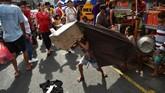 Anak-anak melakukan tarian singa dengan kepala singa yang dibuat dari karton, menghibur pejalan kaki di distrik Chinatown, Manila. (AFP/Ted Aljibe)