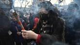 Seorang wanita membakar dupa dan berdoa untuk keberuntungan di Kuil Lama, Beijing, China pada hari pertama Tahun Baru Imlek. (AFP/Grek Baker)