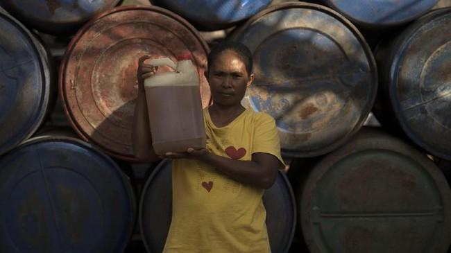 Paulina Rihi Raja menunjukkan bahan bakar minyak yang dibelinya di Agen Premium dan Minyak Solar (APMS) Pulau Sabu, Nusa Tenggara Timur. Paulina yang berprofesi sebagai penjual makanan harus menempuh jarak 10 kilometer berjalan kaki untuk mendapatkan BBM. (ANTARA FOTO/Puspa Perwitasari)
