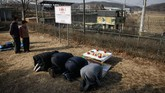 Hanya terlihat segelintir warga Korsel yang berdoa di zona DMZ tersebut, menghadap ke arah Korut, di mana sebagian anggota keluarga mereka berada. (AFP Photo/Ed Jones)