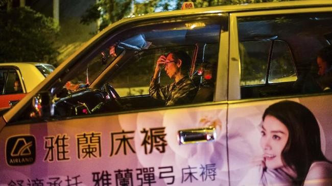 Seorang pengemudi taksi mengistirahatkan mata sambil menunggu lampu lalu-lintas berubah menjadi hijau di suatu jalan di Hong Kong. (Photo by Anthony WALLACE / AFP)