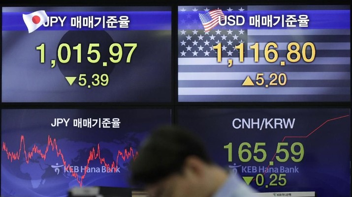 A currency trader walks by screens showing the Korea Composite Stock Price Index (KOSPI), left, and the foreign exchange rate between U.S. dollar and South Korean won at the foreign exchange dealing room in Seoul, South Korea, Thursday, Feb. 7, 2019. Asian shares were mostly higher Thursday on news that the Reserve Bank of Australia may cut interest rates, driving hopes that other central banks could come to the same conclusion. (AP Photo/Lee Jin-man)