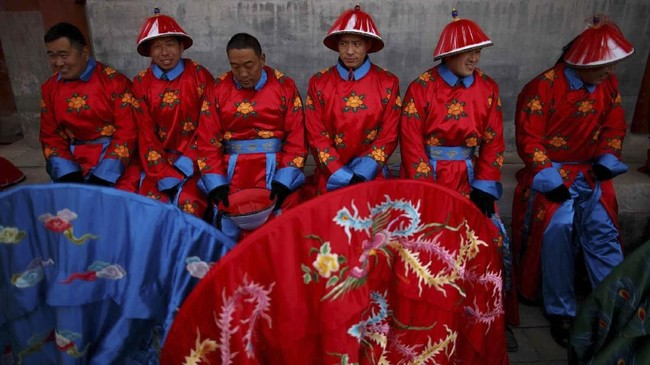 Para seniman beristirahat setelah berlatih adegan reka ulang perayaan Tahun Baru China Dinasti Qing di Kuil Bumi di Taman Ditan, Beijing, China. (REUTERS/Thomas Peter)