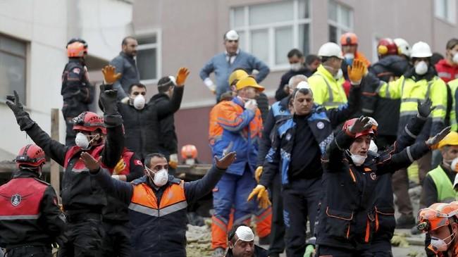 Tim darurat menyelamatkan setidaknya tiga orang, saat banyak orang mengerubungi lokasi kejadian. Jalan menuju bangunan pun terhalang kendaraan dan kerumunan warga. (Reuters/Murad Sezer)