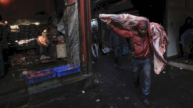 Seorang pekerja India membawa bangkai sapi di atas pundaknya di sebuah pasar daging di daerah kota tua di New Delhi. (Photo by Noemi CASSANELLI / AFP)