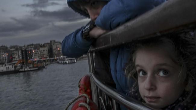 Di atas feri Kadikoy di Bosphorus, Turki, seorang gadis kecil di sela-sela tubuh abangnya melihat ke atas. (Photo by BULENT KILIC / AFP)