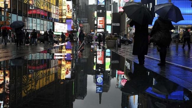 Bayangan orang-orang tercermin di tembok yang terkena hujan di Times Square di New York. Suhu pada awal pekan ini telah kembali ke digit tunggal dan tertinggi selama dua pekan terakhir yaitu 10 derajat celcius. (Photo by TIMOTHY A. CLARY / AFP)
