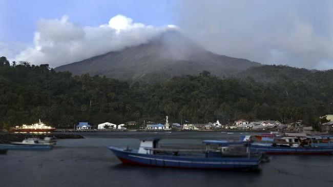 Foto Gunung Karangetang dari kejauhan. Asap putih bertekanan disertai guguran material vulkanik dari kawah bagian utara masih mendominasi aktivitas erupsi efusif Gunung Karangetang. (ANTARA FOTO/Adwit B Pramono)