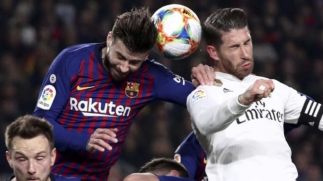 Dua bek tengah kenamaan asal Spanyol, Gerard Pique dan Sergio Ramos, beradu memperebutkan bola dalam sebuah duel udara. (REUTERS/Sergio Perez)