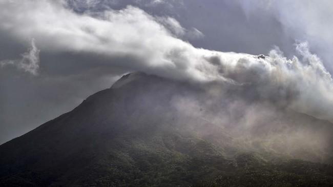 Puncak gunung api Karangetang terpantau dari laut bagian barat Pulau Siau, Kabupaten Kepulauan Sitaro, Sulawesi Utara, Kamis (7/2). Gunung tersebut masih mengeluarkan kepulan asap putih serta muntahan material vulkanik berupa lahar, batuan serta pasir sejauh 3.500 meter dan telah mencapai garis pantai. (ANTARA FOTO)