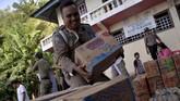Anggota Satpol PP menumpuk pasokan logistik untuk warga di Desa Niambangeng, Siau Barat Utara, Kabupaten Kepulauan Sitaro, Sulawesi Utara, Rabu (6/2). (ANTARA FOTO/Adwit B Pramono)