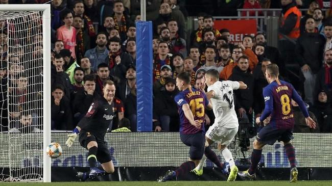Lucas Vazquez menuntaskan sebuah serangan dengan sebuah sentuhan simpel menyambut umpan Karim Benzema untuk membawa Real Madrid memimpin atas Barcelona pada menit keenam. (REUTERS/Albert Gea)