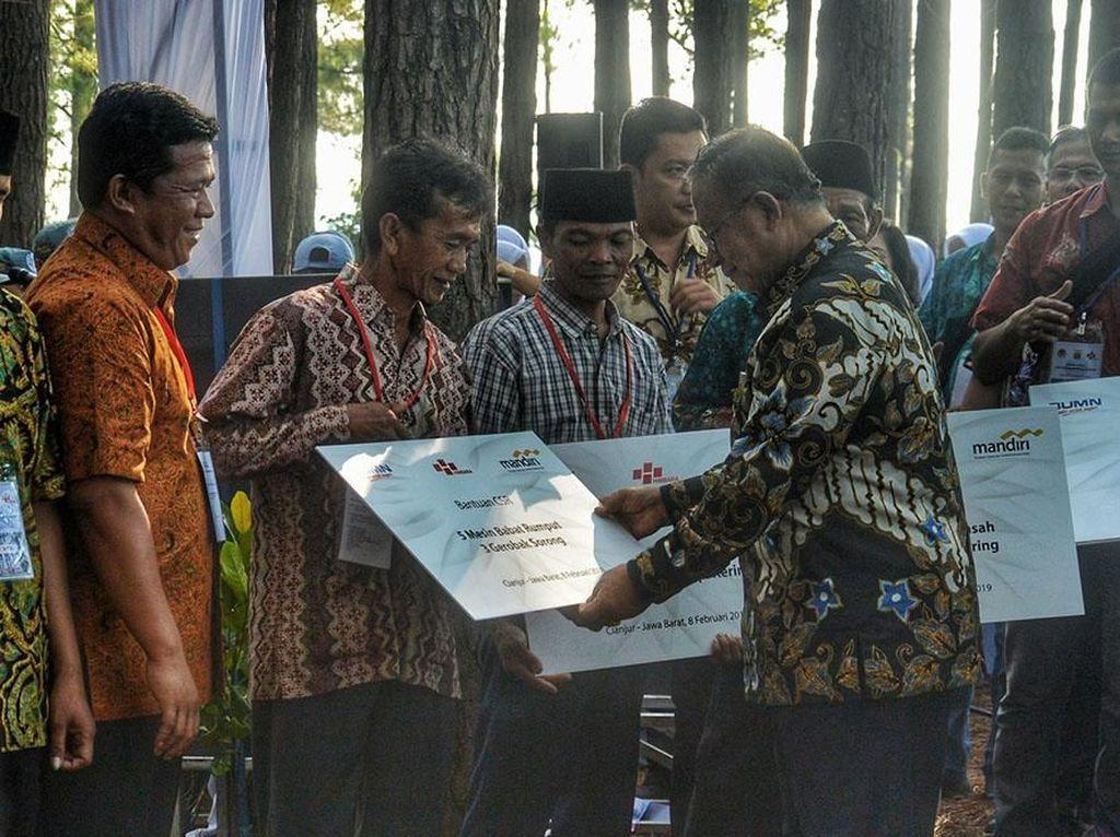 Darmin Nasution secara simbolis menyerahkan bantuan peralatan pertanian dan perkebunankepada petani di wilayah Jawa Barat pada acara perhutanan sosial di Cianjur, Jumat (8/2). Istimewa/Kemenko Perekonomian.