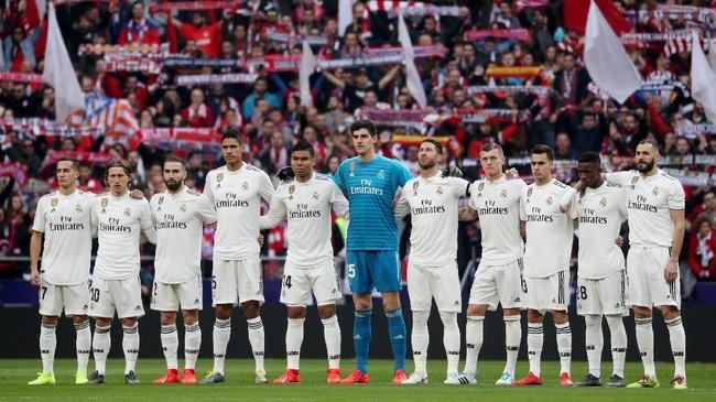 Para pemain Real Madridmengheningkan cipta sebelum melawan Atletico Madrid di Stadion Wanda Metropolitano, Sabtu (9/2), untuk mengenang mendiangIsacio Calleja yang meninggal 4 Februari lalu. (REUTERS/Susana Vera)