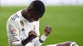 Winger Real Madrid Vinicius Junior bereaksi setelah berhasil memberi penalti untuk Los Blancos usai dijatuhkan Jose Gimenez. Penalti diprotes Atletico Madrid karena menganggappelanggaran terjadi di luar kotak penalti. (GABRIEL BOUYS / AFP)
