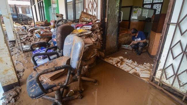 Setelah air surut, kini warga dibantu petugas membersihkan rumah dari endapan lumpur banjir. Warga juga membersihkan barang-barang mereka serta mencari benda berharga yang hilang. (ANTARA FOTO/Raisan Al Farisi/hp)
