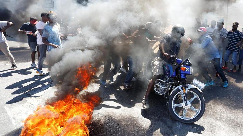 Beberapa demonstrasi berakhir ricuh ketika sejumlah pemrotes bentrok dengan polisi, yang menggunakan gas air mata dan beberapa kali menembakkan peluru ke udara untuk membubarkan massa. (REUTERS/Jeanty Junior Augustin)