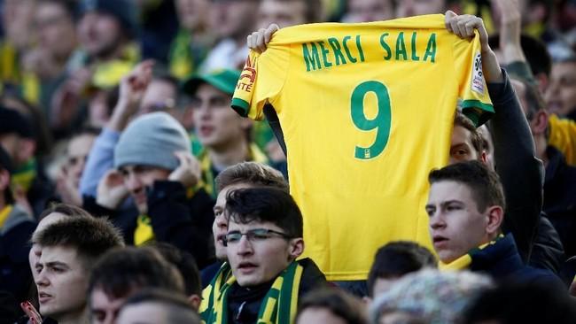Seorang suporter merentangkan kostum replika Nantes bernomor 9 dan bertuliskan 'TERIMA KASIH SALA'. (REUTERS/Stephane Mahe)