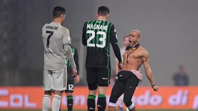 Seorang penyusup melakukan selebrasi khas Cristiano Ronaldo di depan CR7 di sela pertandingan Sassuolo vs Juventus. (REUTERS/Alberto Lingria)