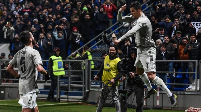 Cristiano Ronaldo (kanan) merayakan gol ke gawang Sassuolo dengan selebrasi yang biasa, namun ditambah dengan selebrasi Dybala Mask yang biasa dilakukan striker Juventus lainnya Paulo Dybala.(Miguel MEDINA / AFP)