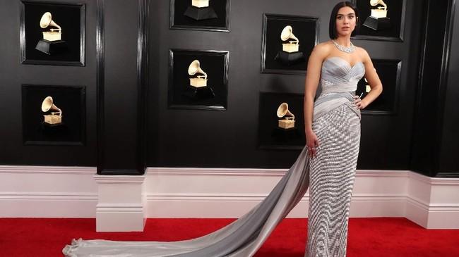 Tak mau kalah dari Lady Gaga, Dua Lipa juga tampil futuristik dengan gaun silver dari Atelier Versace. REUTERS/Lucy Nicholson