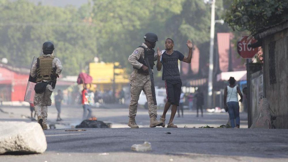 Seorang pemrotes ditahan oleh seorang petugas kepolisian saat melakukan protes dan menuntut pengunduran diri Presiden Jovenel Moise karena tak puas dengan kebijakan ekonominya dan dugaan keterlibatan korupsi di Port-au-Prince, Haiti, Minggu (10/2/2019). (Foto AP/Dieu Nalio Chery)