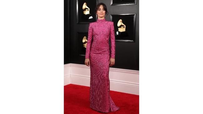 Camila Cabello juga memakai gaun pink body contour berkerah tinggi dan berlengan panjang. Detail sekuin membuatnya terlihat lebih mewah . REUTERS/Lucy Nicholson