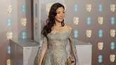 AktrisMichelle Yeoh tampil dengan menggunakan gaun off shoulder dengan lengan cape berwarna biru dengan detail keemasan. (Photo by Tolga AKMEN / AFP)