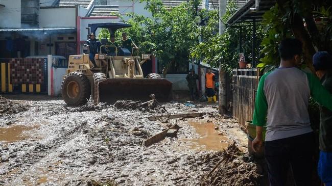 Petugas mengerahkan alat berat untuk mengeruk lumpur pascabanjir bandang yang terjadi Komplek Jati Endah Regency, Pasir Jati, Cilengkrang, Kabupaten Bandung, Jawa Barat. (ANTARA FOTO/Raisan Al Farisi/hp)