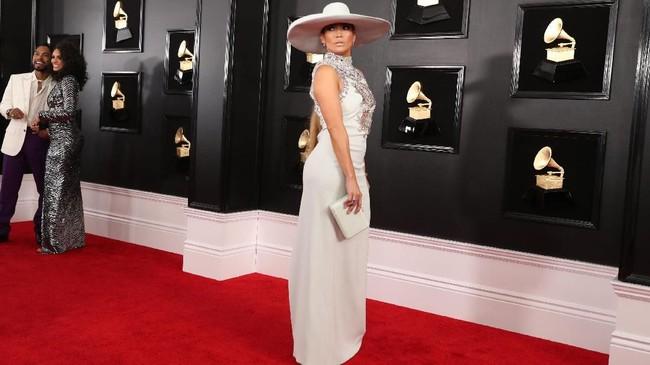 Holiday vibes! Jennifer Lopez dalam balutan gaun Ralph and Russo terlihat sempurna dan elegan. Nilai plus untuk topi putih lebarnya!. REUTERS/Lucy Nicholson