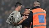 Sang penyusup kemudian memeluk Cristiano Ronaldo sebelum berhasil diamankan petugas. Skor 3-0 untuk Juventus bertahan hingga laga usai. (Miguel MEDINA / AFP)