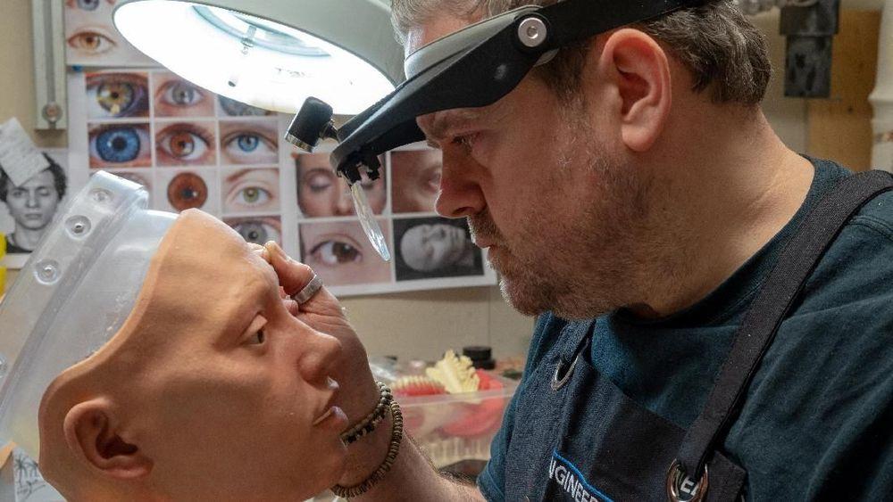 Mike Humphrey, seorang spesialis di perusahaan robotik Engineered Arts, memberikan fitur pada wajah robot Ai-da di Falmouth, Cornwall, Inggris, Kamis (7/2/2019). Robot Ai-da adalahrobot humanoid yang dapatmenyerupai seperti manusia. (REUTERS/Matthew Stock)