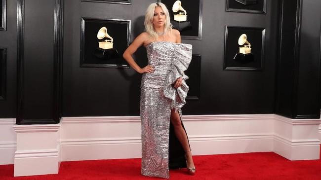 Lady Gaga tampil elektrik dengan gaun straples berwarna silver dari Celine. Tambahan slit panjang dn side rufflesnya menambah glamor gayanya. REUTERS/Lucy Nicholson