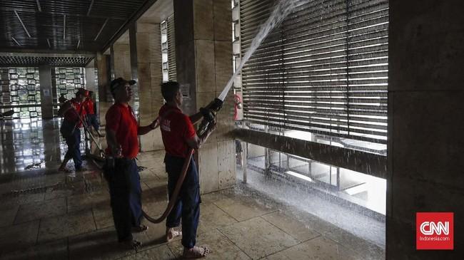 Petugas pemadam kebakaran membersihkan selasar Masjid Istiqlal, Jakarta Pusat, dalam rangka menyambut HUT ke-100 Damkar, Selasa (12/2). Selain Masjid Istiqlal, para petugas pun membersihkan Katedral yang berada di seberangnya.(CNN Indonesia/Adhi Wicaksono)