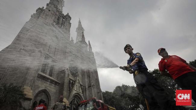 Petugas PMK menyemprotkan air di halaman Gereja Katedral dalam kegiatan Grebek Bersih yang digelar untuk menyambut HUT ke-100 Damkar. (CNN Indonesia/Adhi Wicaksono)