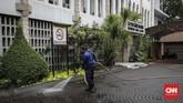 Seorang petugas menyemprot air dengan media selang untuk membersihkan halaman Katedral dalam rangka HUT ke-100 Damkar, Jakarta Pusat, Selasa (12/2). (CNN Indonesia/Adhi Wicaksono)