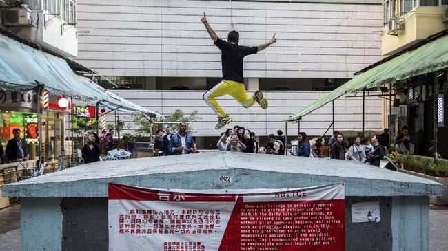 Turis asyik berfoto di balik spanduk larangan berfoto tanpa izin di suatu pemukiman padat di Hong Kong.
